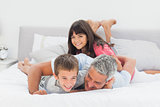 Father having fun with his children on bed