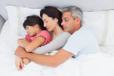 Parents sleeping with their daughter in bed
