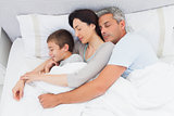 Parents sleeping with their son in bed