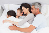Smiling family sleeping together in bed