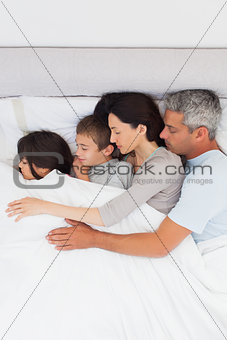 Beautiful family sleeping together in bed