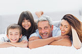 Cute family lying on bed and smiling at camera