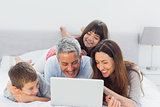 Family lying on bed using their laptop