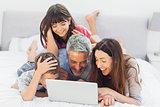 Smiling family lying on bed using their laptop
