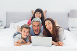 Funny family lying on bed using their laptop