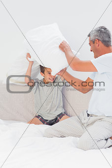 Father and son fighting together with pillows on bed