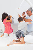 Father and his children fighting together with pillows on bed