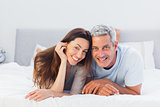 Couple lying on bed and smiling at camera
