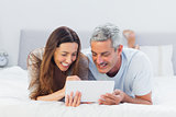 Couple lying on bed using their tablet pc