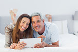 Cheerful couple lying on bed using their tablet pc