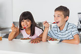 Happy siblings eating cereal for breakfast in kitchen