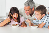 Smiling father talking with his children during their breakfast