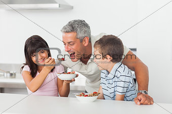Little girl giving cereal to her father with brother smiling