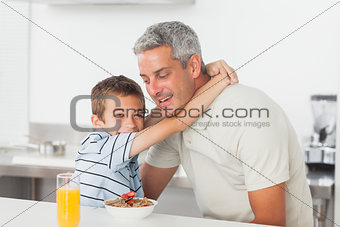 Little boy giving hug to his father during breakfast