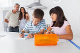 Siblings drawing together in kitchen with their parents smiling