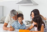 Family drawing together in kitchen