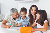 Smiling family drawing together in kitchen