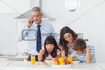Father calling with mobile phone with his family eating breakfast