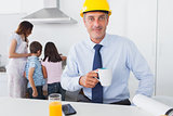 Father wearing hardhat and drinking coffee at home with his family