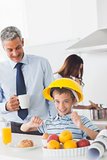 Funny little boy wearing hardhat during breakfast with his parents