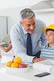 Father showing son his blueprints as he is wearing yellow helmet