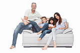 Family sitting on sofa smiling at camera