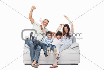 Family sitting on sofa raising their arms
