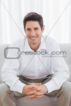 Cheerful young man sitting on sofa