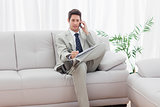 Serious businessman sitting on sofa calling with his mobile phone