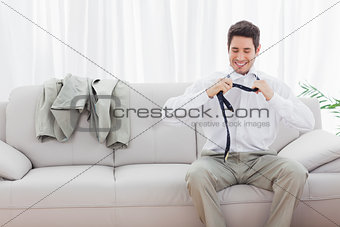 Smiling businessman sitting on sofa loosening his tie