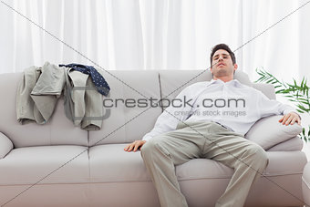 Tired businessman sitting back on sofa