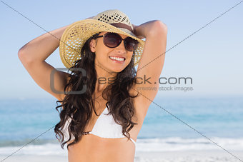 Cheerful attractive brunette with straw hat and sunglasses