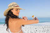 Attractive brunette with straw hat putting on sun cream