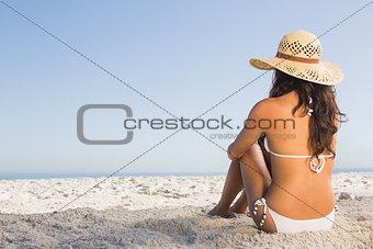 Thoughtful attractive brunette in white bikini sitting