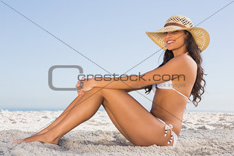 Attractive brunette in white bikini posing while sitting