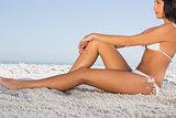 Thoughtful attractive woman in white bikini posing while sitting