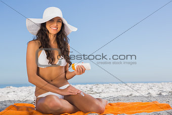 Attractive woman applying sun cream while sitting on her towel