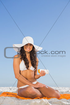 Smiling attractive woman applying sun cream while sitting on her towel