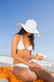 Sexy woman applying sun cream while sitting on her towel