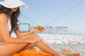 Close up of sexy young woman applying sun cream