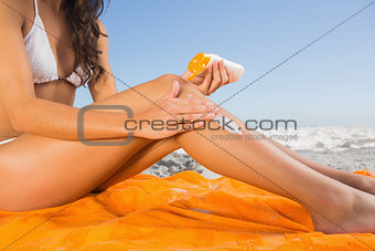 Close up of attractive young woman applying sun cream