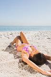 Sexy young woman in pink bikini sunbathing