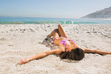 Attractive young woman in pink bikini sunbathing