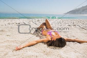 Attractive young woman in pink bikini sunbathing