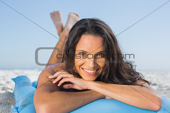 Smiling attractive brunette relaxing on her lilo