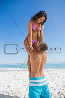 Muscular man holding his girlfriend
