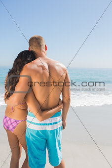 Sexy couple hugging while looking at the sea