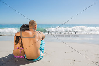 Sexy couple sitting while looking at the sea
