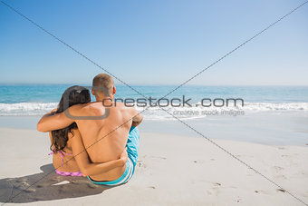 Cute couple sitting while looking at the sea