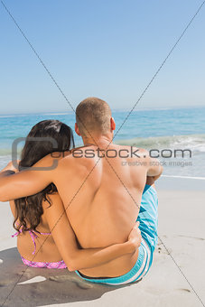Cute young couple sitting while looking at the sea